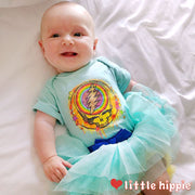 A smiling baby laying on a sheet, wearing the ice blue Rainbow Splatter one piece and a blue Little Hippie tutu.