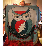 Blonde hippie holding up a blue Grateful Owl cotton woven blanket