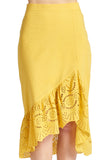 Close-up view of model wearing yellow cotton eyelet asymmetric ruffle hem skirt.