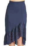 Close-up of model wearing navy cotton eyelet asymmetric ruffle hem skirt.