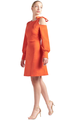 Model wearing fit & flare orange colored long sleeve dress with single shoulder cut-out and shoulder bow-tie.
