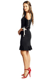 Side view of model wearing above the knee black knit Ponte cold shoulder three quarter sleeve dress with contrast bowties and buttons at sleeves, and ruffles at hems.