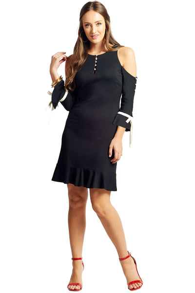 Model wearing above the knee black knit Ponte cold shoulder three quarter sleeve dress with contrast off white buttons, bowties at sleeves, and ruffles at hems.