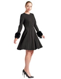 Model twirling in fit & flare black poly crepe long sleeve dress with sweetheart neckline & faux fur cuffs
