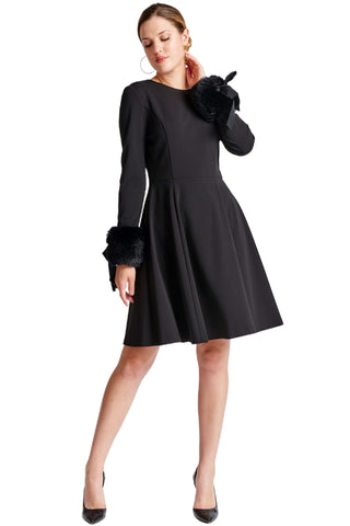 Model wearing fit & flare black poly crepe long sleeve dress with sweetheart neckline & faux fur cuffs.