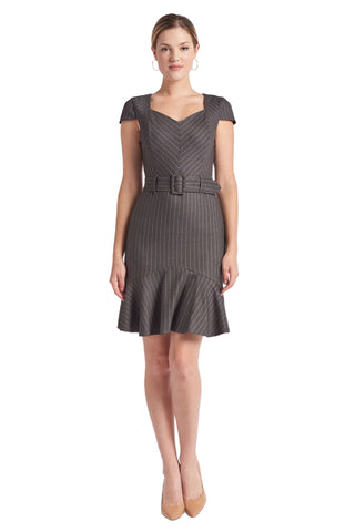 Model wearing charcoal pinstripe above the knee dress with cap sleeves, self belt and ruffle hem.