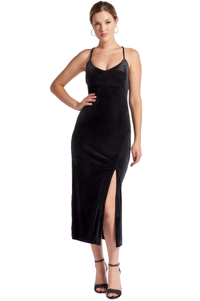 Model wearing black stretch velvet midi dress with thigh high slit, scoop neck and spaghetti straps.