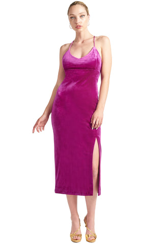 Model wearing magenta stretch velvet midi dress with thigh high slit, scoop neck and spaghetti straps.