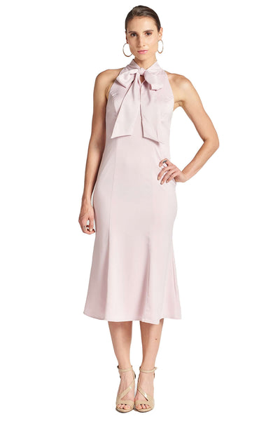 Model wearing light pink stretch satin sleeveless midi dress with pussy bow necktie and mermaid hem.