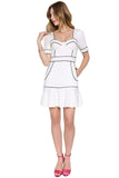 Model wearing white short sleeve knit Ponte bustier mini dress with pockets, ruffle hem and contrast black piping.