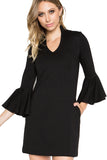 Model wearing black knit Ponte mini shift dress with v-neckline, 3/4 bell sleeves and side slit pockets.