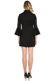 Back view of model wearing black knit Ponte mini shift dress with 3/4 bell sleeves and side slit pockets.