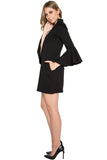 Side view of model wearing black knit Ponte mini shift dress with v-neckline, 3/4 bell sleeves and side slit pockets.
