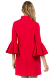 Back view of model wearing red knit Ponte mini shift dress with v-neckline, 3/4 bell sleeves and side slit pockets.