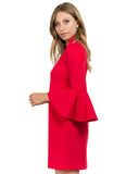 Side view of model wearing red knit Ponte mini shift dress with v-neckline, 3/4 bell sleeves and side slit pockets.
