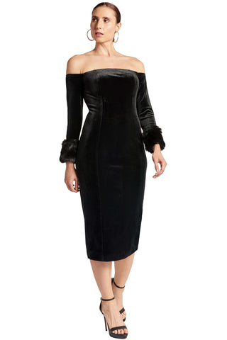 Model wearing off the shoulder black velvet fitted midi dress with long sleeves and faux fur cuffs