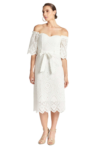 Model wearing white cotton scalloped eyelet midi a-line dress with off the shoulder sweetheart neckline, self belt, and short sleeves.