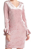 Model wearing pink stretch velvet short dress with v-neckline & long sleeves with bell sleeves.