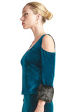 Model wearing teal stretch velvet cut-out cold shoulder top with u-neckline, 3/4 sleeves and black faux fur cuffs.