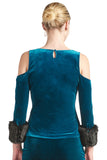 Back view of model wearing teal stretch velvet cut-out cold shoulder top with keyhole back, 3/4 sleeves and black faux fur cuffs.