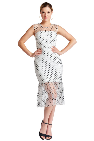 Model wearing white mesh with black polka dots sleeveless midi dress with sheer ruffle hem and round neckline.