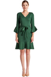 Model wearing green knee length, v-neck knit Ponte dress with 3/4 bell sleeves, ruffle hem and self belt.