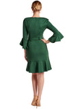 Back view of model wearing green knee length v-neck knit Ponte dress with 3/4 bell sleeves, ruffle hem and self belt.