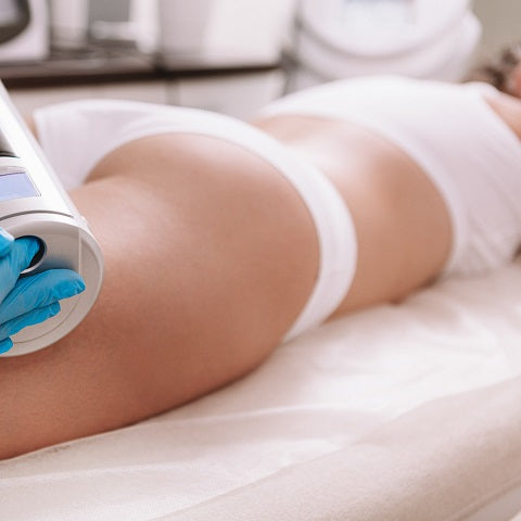 Beautician using endospheres therapy machine on female client, non-invasive body sculpting technique