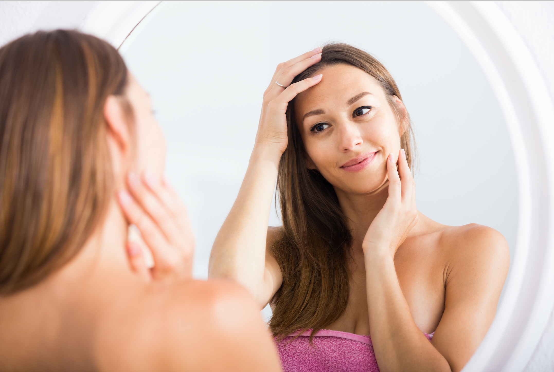 Beautiful Asian American Woman Examining her Glowing Skin in a Mirror | ALASTIN Skincare