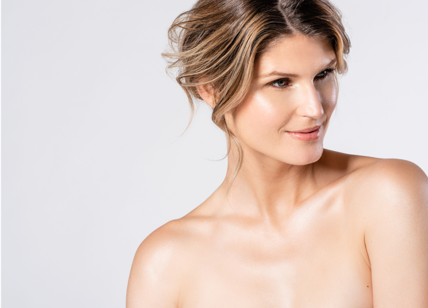 Beautiful blonde woman with glowing skin on neck and chest | ALASTIN Skincare