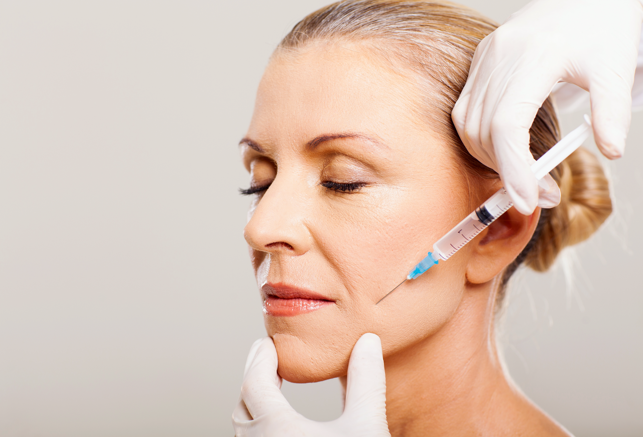 Senior woman getting dermal filler injection | ALASTIN Skincare