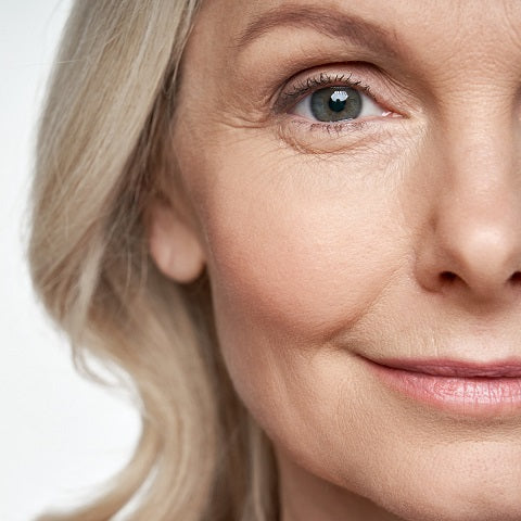 Closeup of pretty middle aged, slightly smiling woman with visible wrinkles