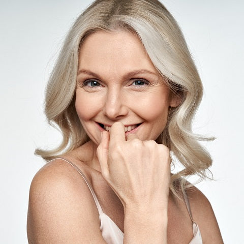 Close up portrait of smiling, attractive, middle aged blonde woman looking at camera.