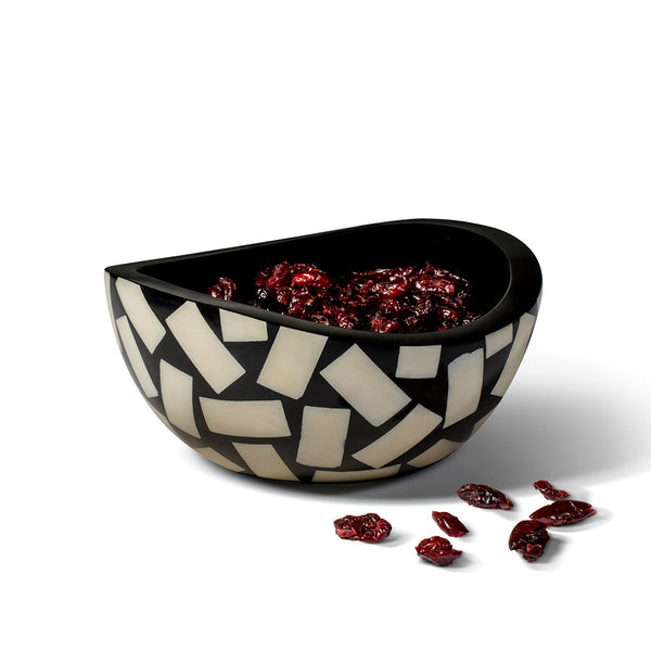 handmade accent bowl black with domino pattern of bone containing dried cranberries