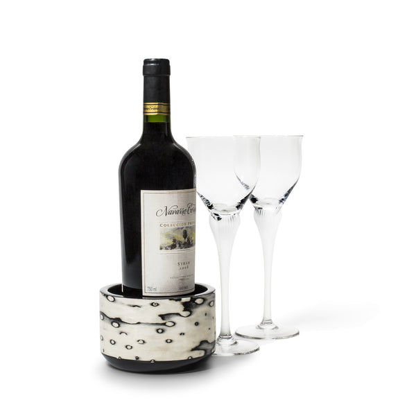 handmade black and cream pattern ojo de pajaro wine bottle coaster with wine bottle inside and two glasses on side