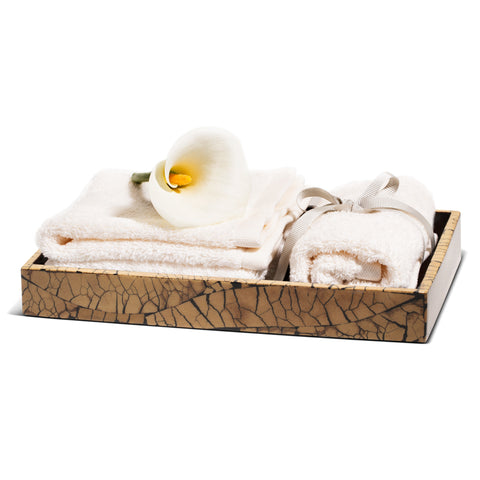 handmade beige and black mosaic patterned totumo wood bath tray with towels and flower inside