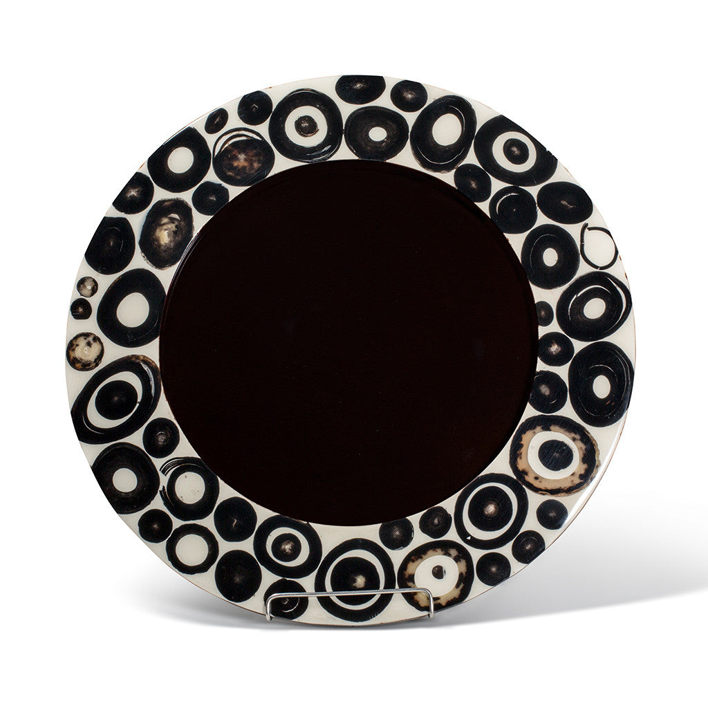 handmade charger plate with circular brown and black horn rings on beige wood