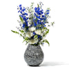 handmade large black wood flower vase with slanted mouth and cream-colored bone with white and blue flowers inside