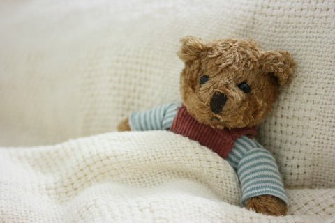 A cute teddy bear lying down in bed