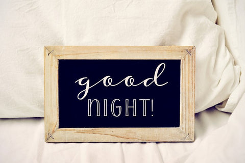 A chalk board on a bed which reads good night!