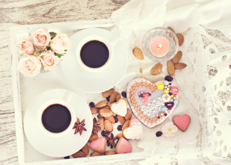 Simple yet elegant breakfast in bed with coffees and heart shaped biscuits