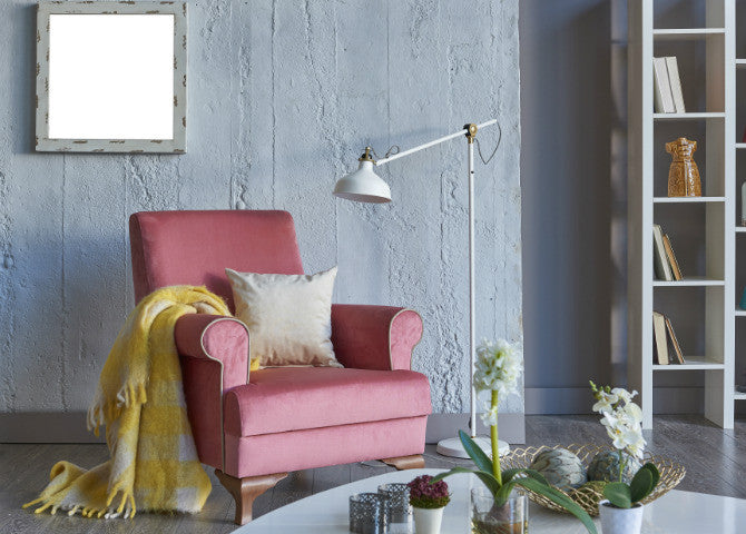 A pale red armchair in front of a grey wall