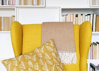 Yellow armchair draped with a beige throw with white tassels