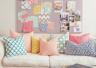 Cream living room with cream sofa draped with white, teal, pink, yellow and blue geometric patterned cushions