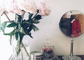 Light pink flowers in a glass vase on side table in a white room