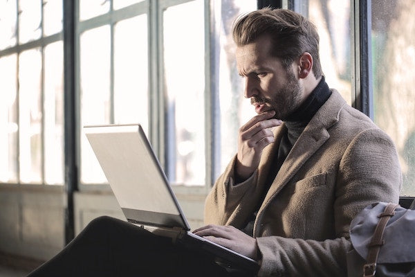 Man sitting at computer, contemplating giving us his email