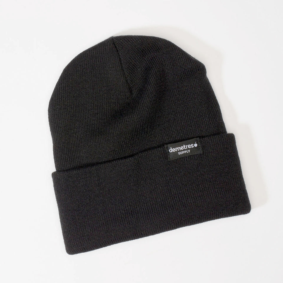 Solid black cuffed knit beanie with a black woven label.