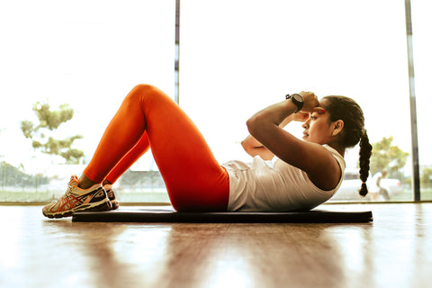 Woman working out at gym wearing orange trousers
