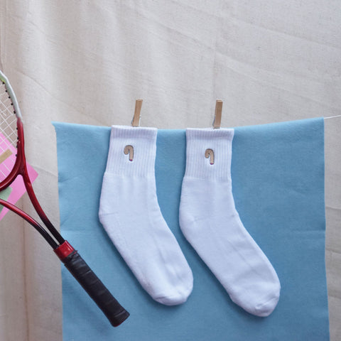 white cotton sports socks and a tennis racket on a blue background