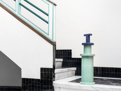 Example of a 1980's staircase decorated with black subway tiles, white marble floors, and an aqua bannister